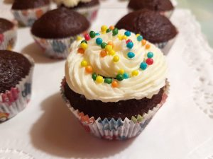 Chocolate cupcake decorated with buttercream frosting and sprinkles